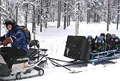 Excursión-en-motonieve-para-niños,-el-guía-tira-de-del-trineo-donde-van-los-niños